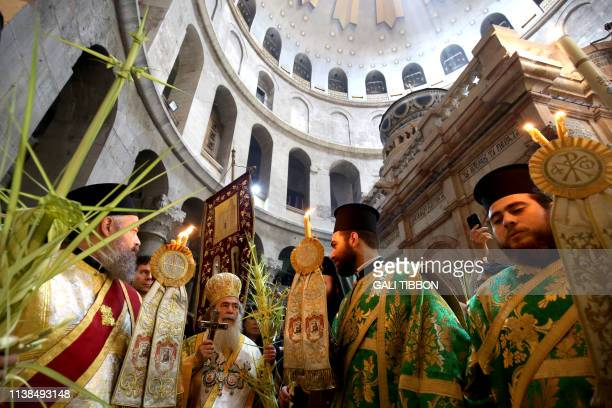 Greek Orthodox priests pray during the Palm Sunday procession at the Church of the Holy Sepulchre in Jerusalem's Old City on April 21 2019 Hundreds...