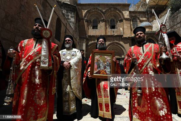Greek Orthodox priests take part in the Easter Sunday procession in front of the Church of the Holy Sepulchre in Jerusalem's Old City on April 28 as...