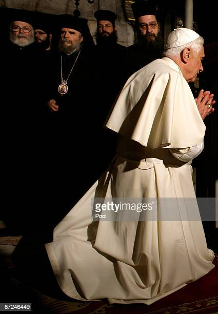 Greek Orthodox Priests watch as Pope Benedict XVI prays in the Golgotha or Calvary the traditional site where Jesus was crucified in the Church of...