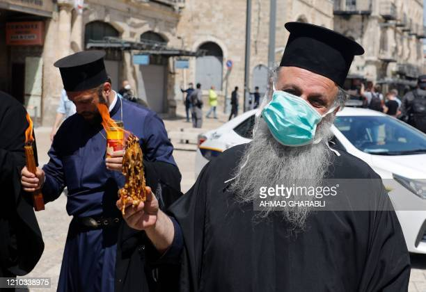 Greek Orthodox priests wearing a protective masks hold up candles lit from the Holy Fire in the church of the Holy Sepulchre as very few Orthodox...