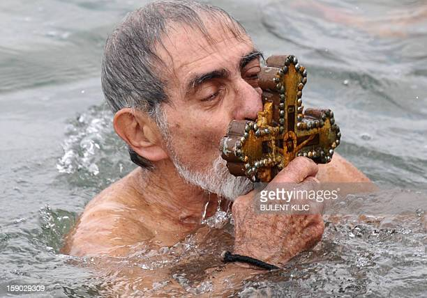 A Greek Orthodox swimmer kisses the wooden cross he rtrieved from the Bosphorus river's Golden Horn after a mass as part of celebrations of the...