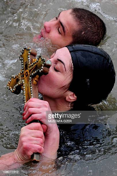 A Greek Orthodox swimmer kisses the wooden cross in the Bosphorus river's Golden Horn after a mass as part of celebrations of the Epiphany day at the...