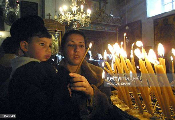 Greek Orthodox woman lights candles with her child on Christmas Day at Bethlehem's Church of the Nativity the traditional birthplace of Jesus Christ...