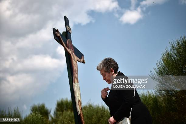 Greek Orthodox worshipper prays and kisses a wooden crucifix during a Good Friday's Apokathelosis, the lowering of Christ's dead body from the Cross,...