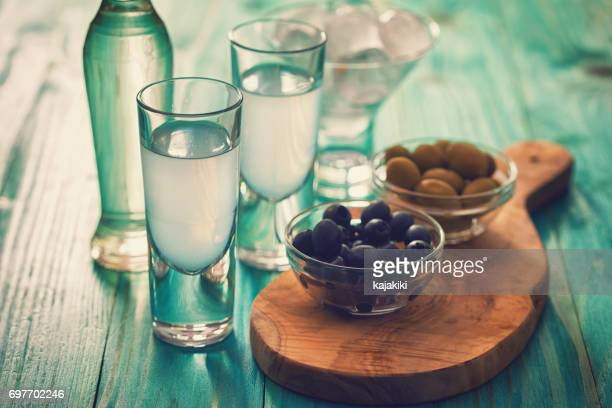 greek ouzo and olives - kalamata olive stock photos and pictures