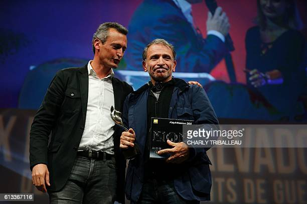 Greek photographer Yannis Behrakis reacts after receiving the Photo Trophy awarded by Nikon during the closing ceremony of the 2016 BayeuxCalvados...