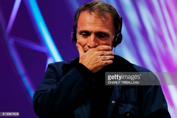 Greek photographer Yannis Behrakis reacts as he receives the Photo Trophy awarded by Nikon during the closing ceremony of the 2016 Bayeux-Calvados...