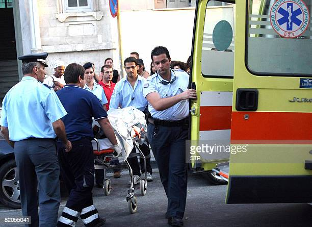 Greek police and medics escort British Leah Andrews to the ambulance after she allegedly fainted in the prosecutor's office at Heraklion town on...