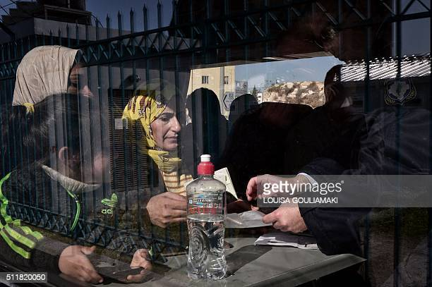 Greek police checks the documents of Syrian and Iraqi refugees aboard a bus taking them to the Greek-Macedonian border in the port of Piraeus on...