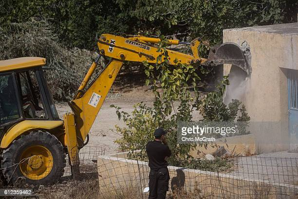 A greek police officer watches on as a bulldozer demolishes the last room of the farmhouse at the search site of missing toddler Ben Needham on...
