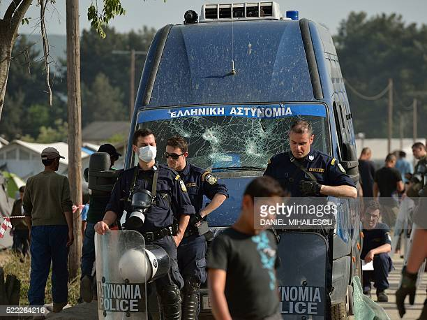 Greek police officers stand guard after migrants and refugees threw stones at a police van that was involved in an accident that seriously injured a...