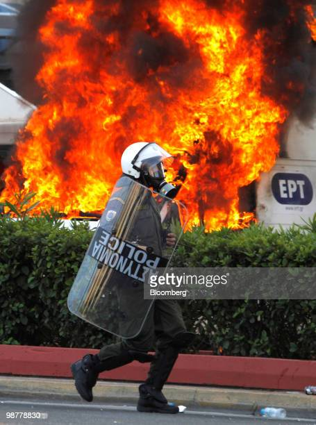A Greek policeman runs past a burning vehicle set alight by protesters in Athens Greece on Saturday May 1 2010 Greek Finance Minister George...