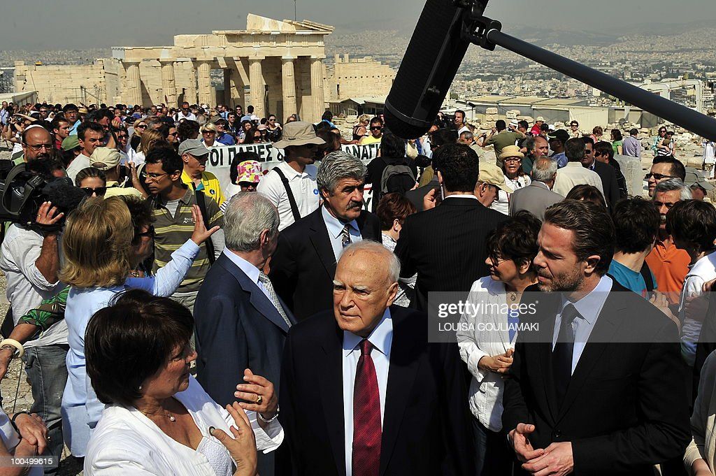 Greek president Carolos Papoulias (C) and Culture Minister Pavlos Geroulanos (R) are informed about the restoration works while Ministry of Culture employees protest behind at the Acropolis archaeological site on May 25, 2010. Greek state employees hijacked a restoration event at the Acropolis in Athens on Tuesday as the government tries to force through unpopular wage cuts and hiring freezes to cut massive debt. Around 200 culture ministry staff staged a protest at the Acropolis, Greece's best-known ancient monument, to demand permanent jobs after being hired on short-term contracts for years. AFP PHOTO / Louisa Gouliamaki