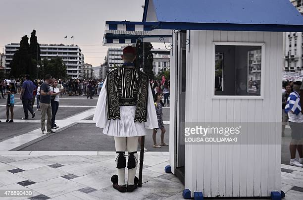 A greek presidental guard stands at his post in front of the Greek parliament during a demonstration calling for a 'NO' at a referendum and for...