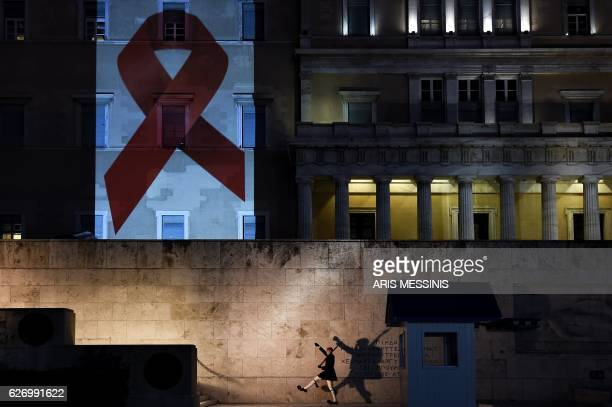 A Greek Presidential guard performs in front of the tomb of the Unknown soldier as the Greek parliament is illuminated with the Red Ribbon logo of...