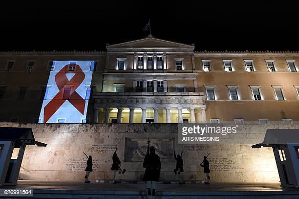 Greek Presidential guards perform in front of the tomb of the Unknown soldier while the Greek parliament is illuminated with the Red Ribbon logo of...