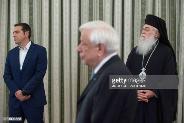 Greek Prime Minister Alexis Tsipras and Bishop of Methoni Klimis look on as Greek President Prokopis Pavlopoulos leads a swearingin cermony of the...