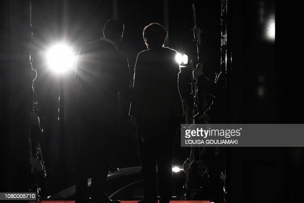 TOPSHOT Greek Prime Minister Alexis Tsipras and German Chancellor Angela Merkel are seen in silhouette while shaking hands upon Merkel's arrival in...