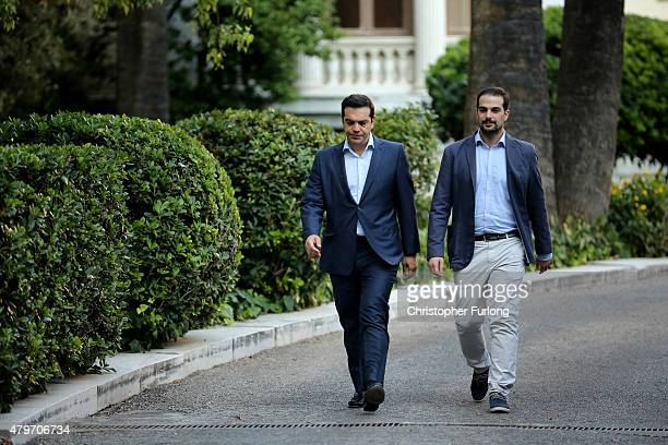 Greek Prime Minister Alexis Tsipras and government spokesman Gabriel Sakellaridis leave the presidential palace after the swearing in ceremony of the...
