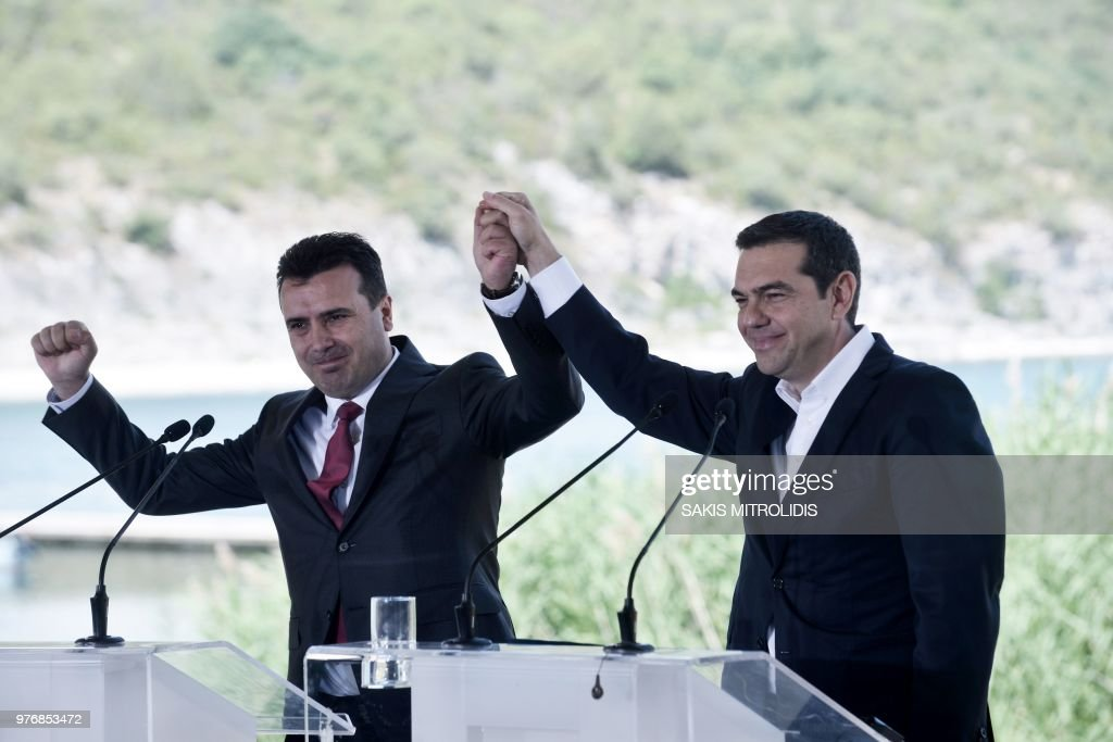 TOPSHOT - Greek Prime Minister Alexis Tsipras (R) and Macedonian Prime Minister Zoran Zaev raise their hands during a signing ceremony between officials from Greece and Macedonia at Prespes Lake on June 17, 2018. - The foreign ministers of Greece and Macedonia on June 17, 2018 signed a historic preliminary accord to end a 27-year bilateral row by renaming the small Balkan nation the Republic of North Macedonia.