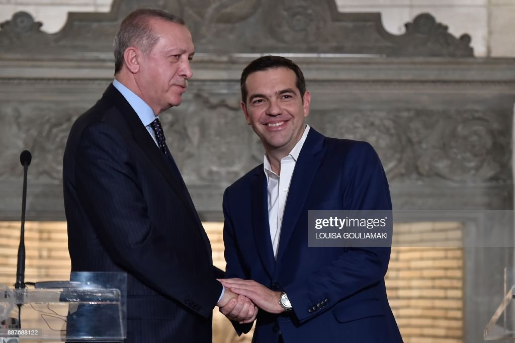 Greek Prime Minister Alexis Tsipras (R) and Turkish President Recep Tayyip Erdogan shake hands after delivering a joint press conference in Athens on December 7, 2017. President Recep Tayyip Erdogan began a state visit to Greece on December 7, the first by a Turkish head of state in 65 years, by needling his hosts with revisionist border talk and complaints about its treatment of Muslims. /
