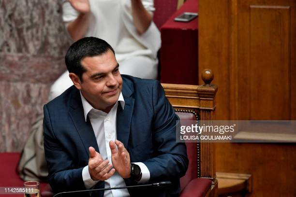 Greek Prime Minister Alexis Tsipras applauds during a parliamentary debate prior to the confidence vote at the Greek parliament in Athens on May 10...