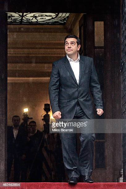 Greek Prime Minister Alexis Tsipras checks the weather as he awaits European Parliament President Martin Schulz at his office prior to their meeting...