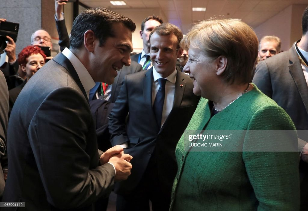 TOPSHOT - Greek Prime minister Alexis Tsipras, French president Emmanuel Macron (C) and German chancellor Angela Merkel (R) smile as they talk in a corridor at the end of the European Council on March 23, 2018, in Brussels. / AFP PHOTO / Ludovic MARIN