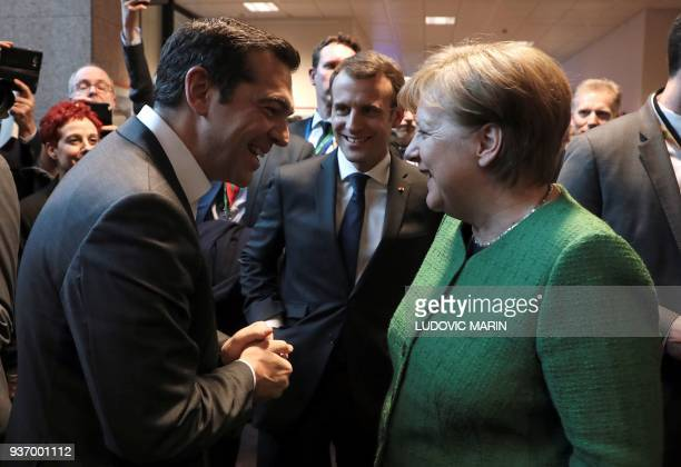 TOPSHOT Greek Prime minister Alexis Tsipras French president Emmanuel Macron and German chancellor Angela Merkel smile as they talk in a corridor at...