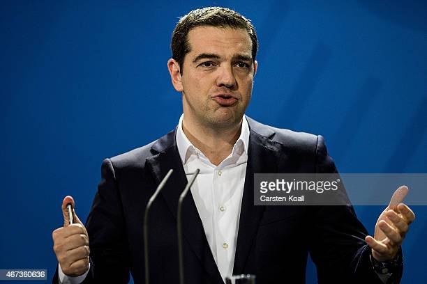 Greek Prime Minister Alexis Tsipras gestures while he and German Chancellor Angela Merkel speak to the media following talks at the Chancellery on...