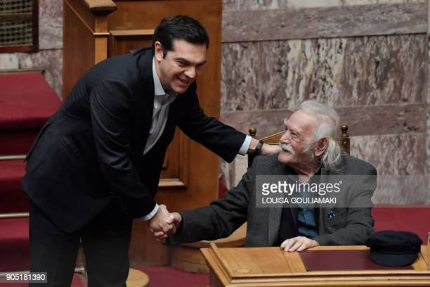 Greek Prime Minister Alexis Tsipras greets politician and resistance hero Manolis Glezos prior to his speech at the Greek parliament in Athens on...