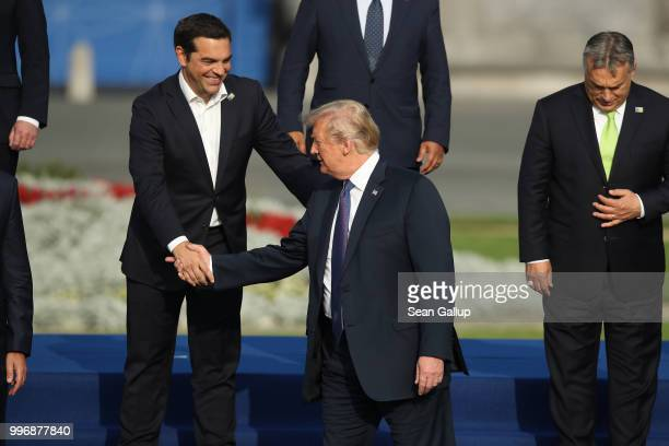 Greek Prime Minister Alexis Tsipras greets US President Donald Trump prior to a group photo at the evening reception and dinner at the 2018 NATO...