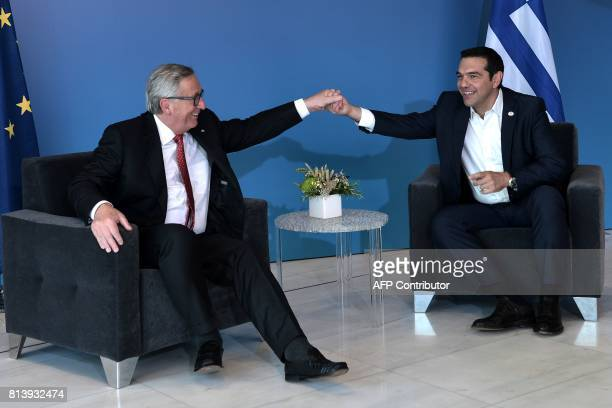 Greek Prime Minister Alexis Tsipras holds hands with President of the European Commission JeanClaude Juncker as they meet ahead of a ceremony to...