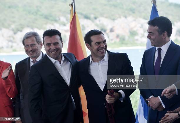 Greek Prime Minister Alexis Tsipras holds the tie of Macedonian Prime Minister Zoran Zaev as EU enlargement commissioner Johannes Hahn and Macedonian...