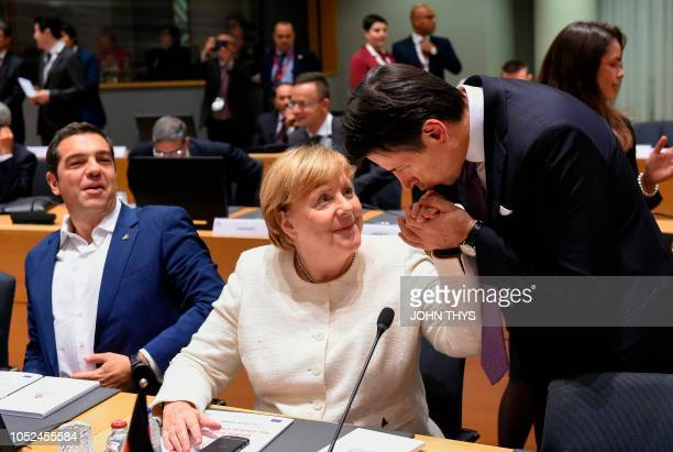 Greek Prime Minister Alexis Tsipras looks on as German Chancellor Angela Merkel has her hand kissed by Italy's Prime Minister Giuseppe Conte ahead of...