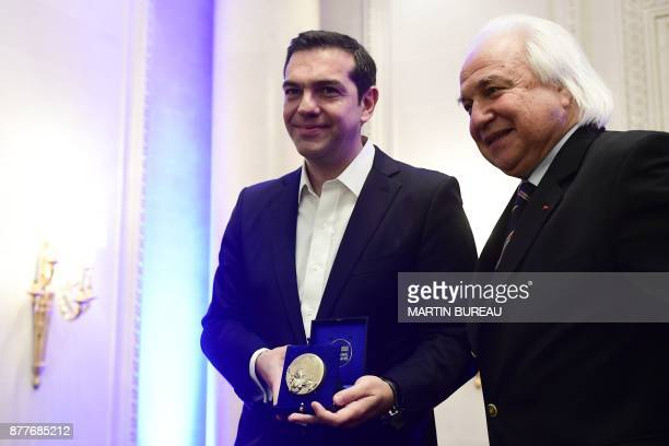 Greek Prime Minister Alexis Tsipras poses with International Politics magazine director Patrick Wajsman after receiving a prize rewarding political...