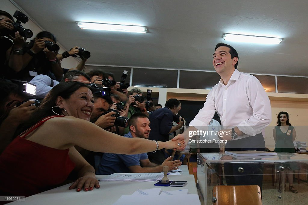 Greek Prime Minister Alexis Tsipras shakes hands with an official after placing his referendum vote in the ballot box at a school in the suburbs of Athens on July 5, 2015 in Athens, Greece. The people of Greece are going to the polls to decide if the country should accept the terms and conditions of a bailout with its creditors. Greek Prime Minister Alexis Tsipras is urging people to vote 'a proud no' to European creditors' proposals, and 'live with dignity in Europe'. 'Yes' campaigners believe that a no vote would mean financial ruin for Greece and the loss of the Euro currency.
