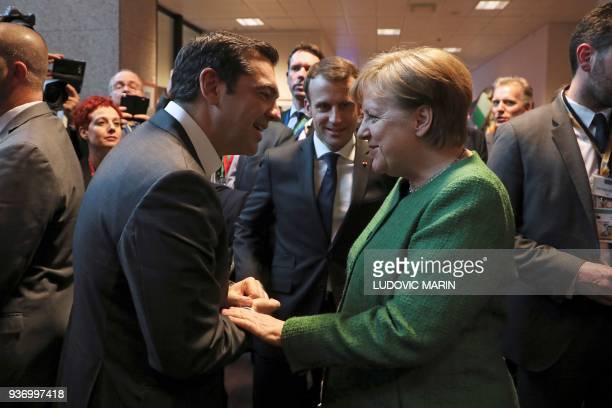 Greek Prime minister Alexis Tsipras shakes hands with German chancellor Angela Merkel next to French president Emmanuel Macron as they meet in a...