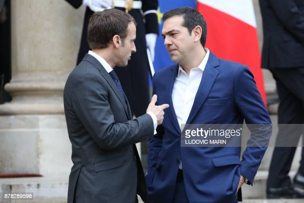 Greek Prime Minister Alexis Tsipras speaks with French President Emmanuel Macron as he leaves the Elysee Palace after a meeting on November 24 2017...