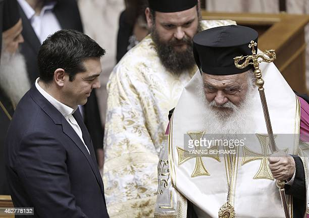 Greek Prime Minister Alexis Tsipras stands next to Greek Archbishop Ieronimos during a swearingin ceremony of the new deputies that were elected in...