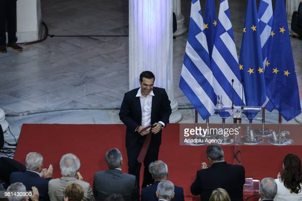 Greek Prime Minister Alexis Tsipras takes out his tie as he delivered a speech to lawmakers at the parliamentary group of Syriza and Independent...