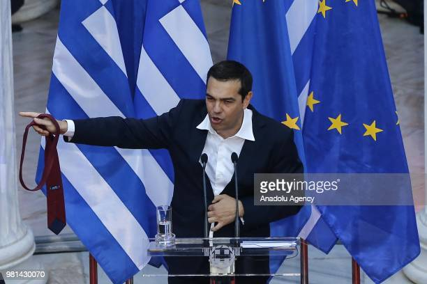 Greek Prime Minister Alexis Tsipras takes out his tie as he delivers a speech to lawmakers at the parliamentary group of Syriza and Independent...