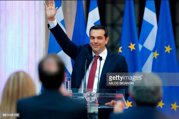 Greek Prime Minister Alexis Tsipras wearing a tie waves before addressing the parliamentary group of leftist Syriza and coalition partner Independent...