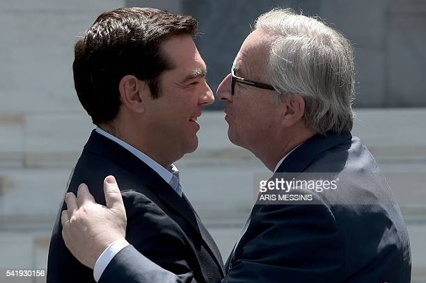 Greek Prime Minister Alexis Tsipras welcomes the President of the European Commission JeanClaude Juncker before their meeting in Athens on June 21...