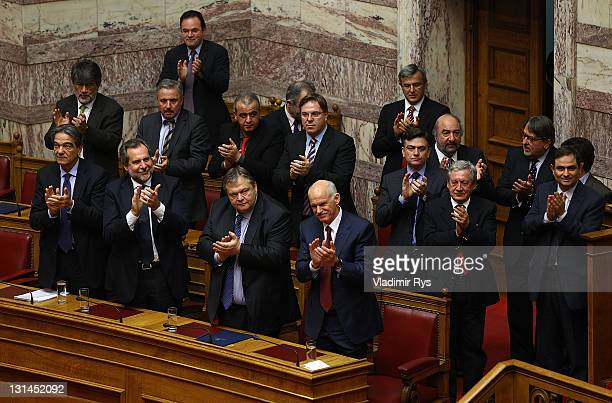 Greek Prime Minister George Papandreou and members of his government applaud after winning the confidence vote in the Greek parliament on November 04...