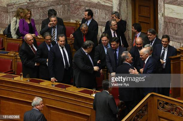 Greek Prime Minister George Papandreou and members of his government congratulate each other after winning the confidence vote in the Greek...