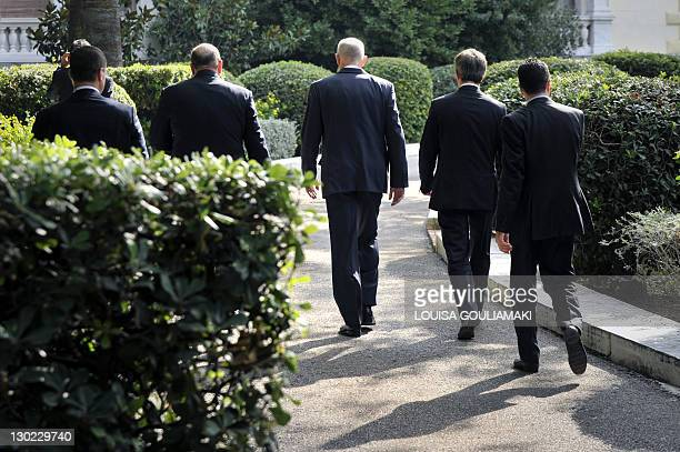 Greek prime Minister George Papandreou flanked with his aides and security arrives to the Presidental Palace to attend a meeting with Greek President...