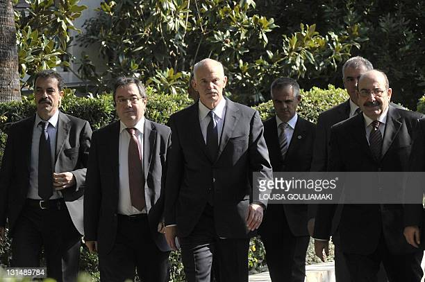 Greek Prime Minister George Papandreou is flanked by his aides and security while leaving the Presidental Palace in Athens after his talks with Greek...