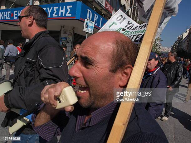 CONTENT] Greek protester shouting into a megaphone while marching in the streets