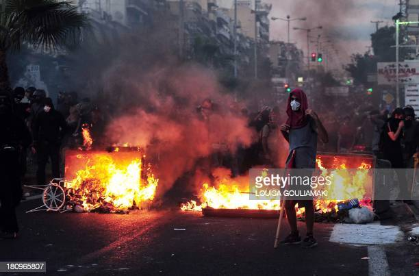 Greek protester stands in front of burning garbage as thousands gather in Keratsini, a western suburb of Athens, after a musician was murdered by a...